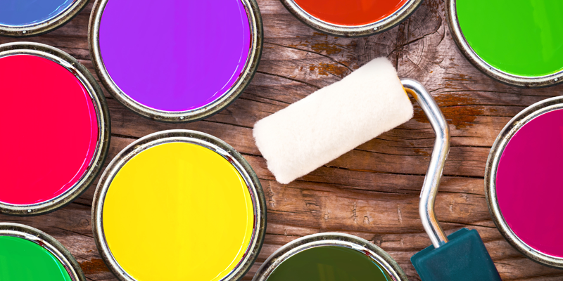 Colourful paint tins and a roller
